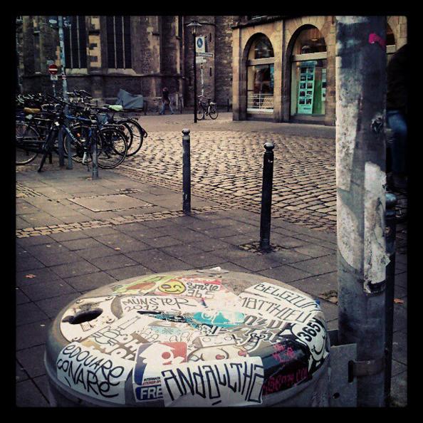 Une jolie collection d'imprimés autocollants exposée sur une poubelle à Münster — avec Obit, freaQ, PQ Family, Wojo, Oh,No!John!, Smile 365, Kse, edouare conare et Andalltha