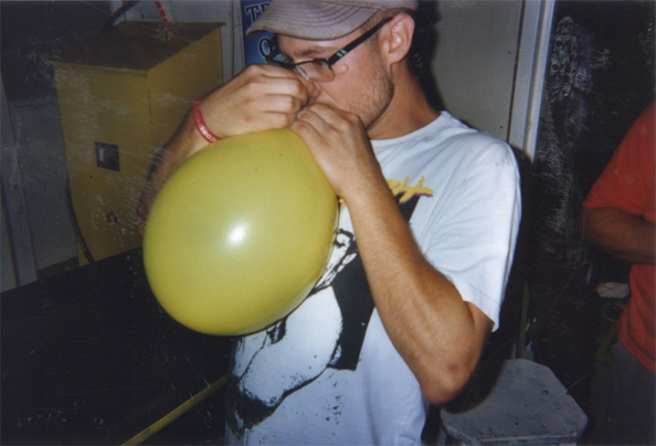 Inhaling laughing gas from a balloon in Sunny Beach, Bulgaria